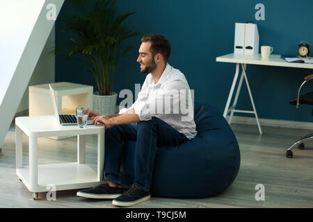 Young businessman with laptop working in office - Stock Photo