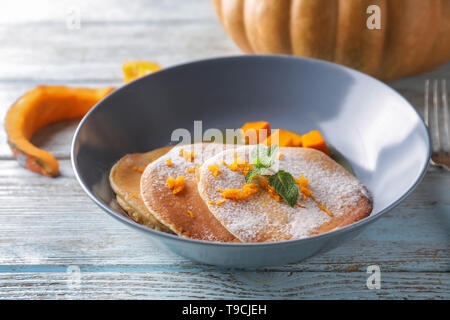 Hot tasty pancakes with pumpkin and honey in bowl on wooden table - Stock Photo