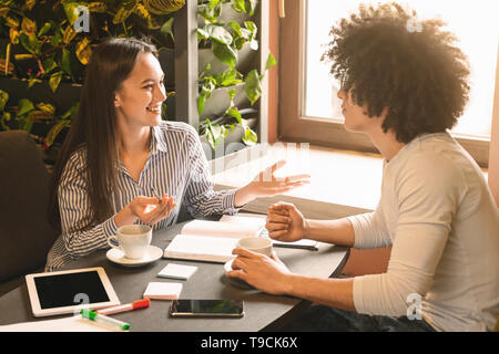 Cheerful woman talking with new candidate in cafe - Stock Photo