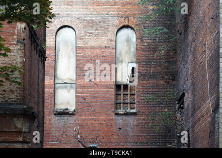 Old arched windows in a brick wall of an old destroyed building, background or concept. - Stock Photo
