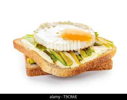 Tasty toasted bread with avocado and fried egg on white background - Stock Photo