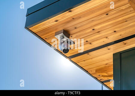 Home with security camera installed on the wooden underside of its roof - Stock Photo