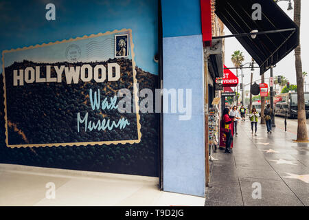 Hollywood Walk of Fame at Morning. Corner of Hollywood Wax Museum and tourists walking on the stars. Los Angeles, Hollywood, California, May 14,  2019 - Stock Photo