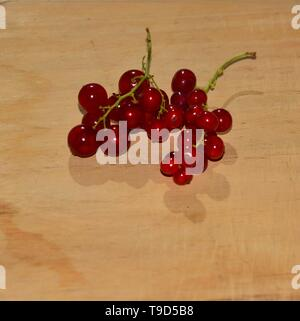 Red currant berries isolated on a wooden background. - Stock Photo