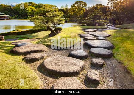 9 April 2019: Tokyo, Japan - Kiyosumi Garden, stepping stones beside the lake. Flare as sun sets on top right. - Stock Photo