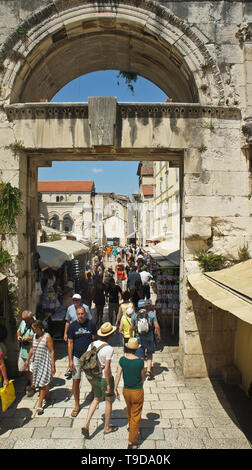 People walking through Eastern (Silver) Gate, part of Diocletian Palace, sunny day, Dalmatia - Stock Photo