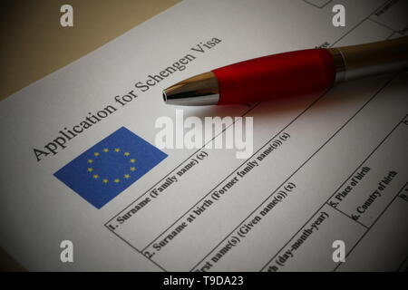 EU Schengen Visa application form with a pen for filling out. Document For applying to entry in the European Union. - Stock Photo