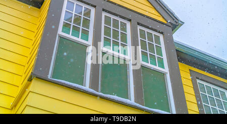 Home in Daybreak Utah with yellow exterior wall and reflective glass windows - Stock Photo