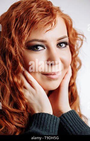 Charming, pretty, cute, lovely redhead woman touching cheeks with both palms, enjoying her perfect face skin after cream, mask, lotion, peeling. Head  - Stock Photo