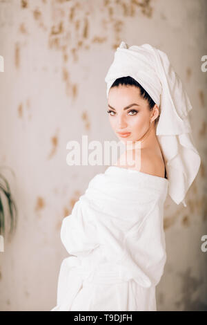 Beautiful young woman in white bathrobe with towel on her head posing, looking at camera with serious expression, standing with bare shoulders, restin - Stock Photo