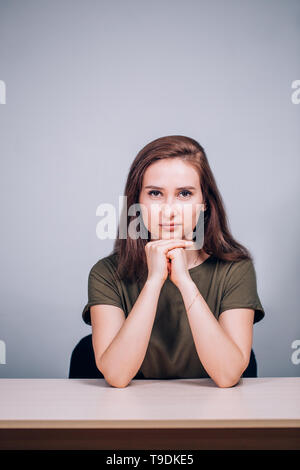 Portrait of a beautiful business woman in the office at the table. The girl looks seriously into the camera - Stock Photo
