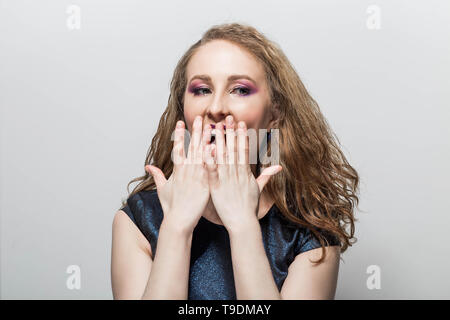 Surprised young curly woman. smiles positive emotion - Stock Photo