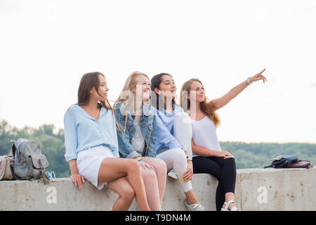 Happy Friends On Picnic Outdoors. Young Smiling People Sitting on concrete border and one girl pointing up - Stock Photo