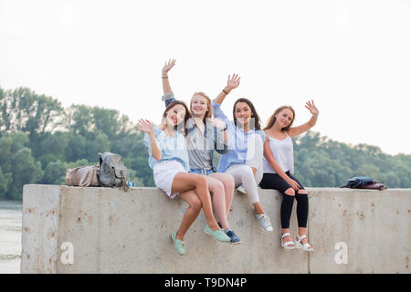 Happy female Friends Having Fun On Weekend, On Picnic Outdoors. Young Smiling People Sitting on concrete border and looking at camera - Stock Photo