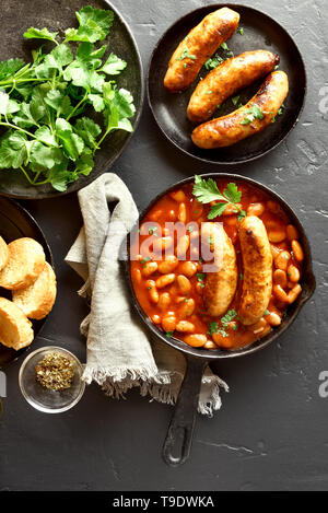 Sausages with baked white beans in tomato sauce in frying pan over black stone background. Top view, flat lay - Stock Photo