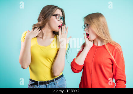 Two young women are surprised and shocked by the news, emotionally talking about something - Stock Photo