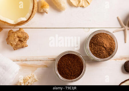 Spa decoration, natural organic body care products. Beautiful composition with coconut, coffee scrub, flower, sea shell, white towel on vintage wooden - Stock Photo