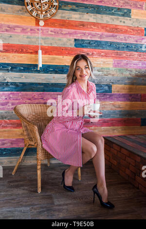 Beautiful fashionable blonde woman in a pink striped dress and enjoy your morning coffee. Happiness, positive emotions, lifestyle concepts - Stock Photo