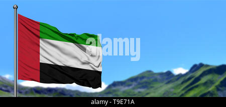 United Arab Emirates flag waving in the blue sky with green fields at mountain peak background. Nature theme. - Stock Photo