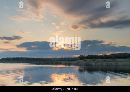 Sun Behind Storm Clouds Over Large Texas Lake in Summer - Stock Photo