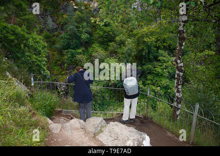 Ein Mann und eine Frau stehen am Aussichtspunkt vom Wasserfall fall of Foyers in Schottland - Stock Photo