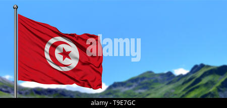 Tunisia flag waving in the blue sky with green fields at mountain peak background. Nature theme. - Stock Photo