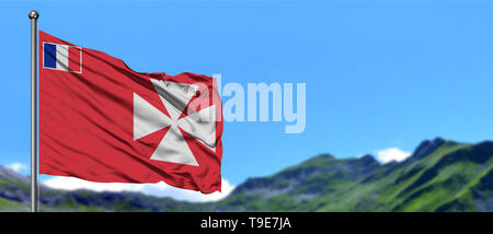Wallis And Futuna flag waving in the blue sky with green fields at mountain peak background. Nature theme. - Stock Photo