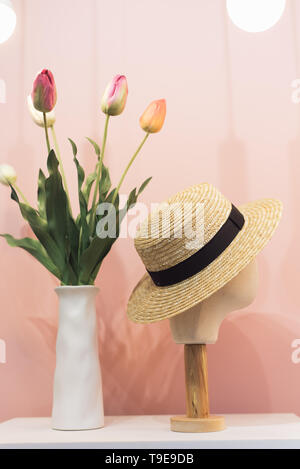 Mannequin head in straw hat on shop window. Hat in the mall on a pastel pink background next to tulips in a vase - Stock Photo