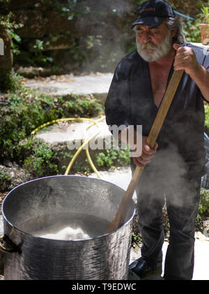 Traditional Cretan man with white beard making wedding rice for a taverna in a village in Crete Greece - Stock Photo