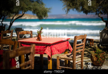 Evocative picture of a Greek taverna on the beach in Crete with the sea in background - Stock Photo