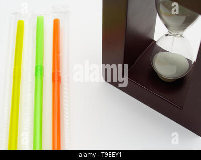 Three colored plastic straws and a hourglass. White background with empty space for caption. Plastic straws are being banned in various countries arou - Stock Photo