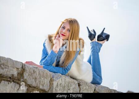 Teen girl crossed-legs Black heels pumps trousers MR eyeshot looking at camera eyes-eye contact highheelslover - Stock Photo