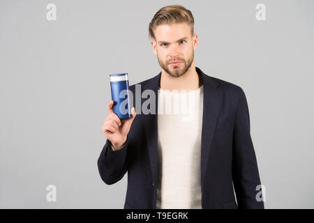 Man confident face holds shampoo bottle, grey background. Guy with bristle holds bottle shampoo, copy space. Man enjoy freshness after washing hair wi - Stock Photo