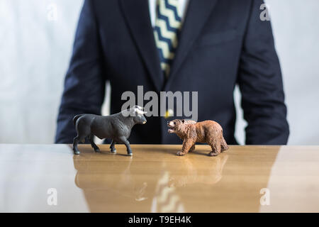 Stock market, securities trading and capitalism concept with a bull and bear concepts. Business trader man in suit in background. - Stock Photo