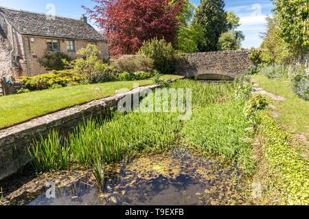 Glebe Field Cottage beside an old mill leat in the Cotswold town of Northleach, Gloucestershire - Stock Photo