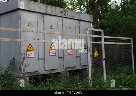 Outdoor electric power thansformer box with yellow hazard signs - Stock Photo