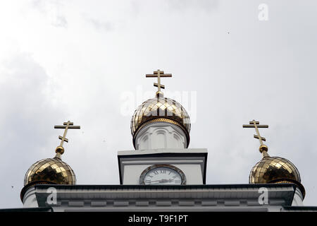 Golden domes of the Orthodox Church against the sky on a cloudy day
