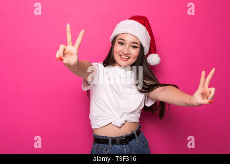 Young asian woman wearing christmas hat over isolated over pnk background smiling with happy face winking at the camera doing victory sign. - Stock Photo