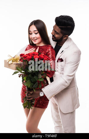 Beautiful romantic asian couple, young asian woman in dress holding red roses and handsome indian man in suit are in love isolated on white background - Stock Photo