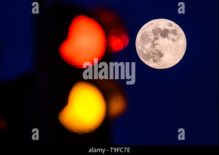 Brake, Germany. 18th May, 2019. The full moon can be seen in the sky next to a traffic light that changes from red to yellow. Credit: Mohssen Assanimoghaddam/dpa/Alamy Live News - Stock Photo