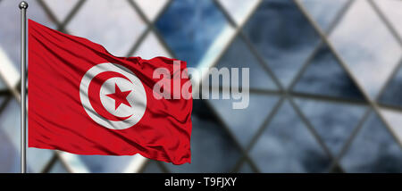 Tunisia flag waving in the wind against blurred modern building. Business concept. National cooperation theme. - Stock Photo