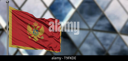 Montenegro flag waving in the wind against blurred modern building. Business concept. National cooperation theme. - Stock Photo