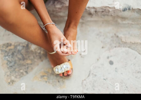 Tourist woman with sore feet and blisters checks her aching feet. - Stock Photo