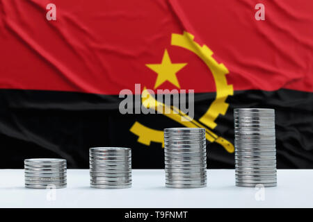 Wrinkled Angola flag in the background with rows of coins for finance and business concept. Saving money. - Stock Photo