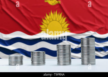 Wrinkled Kiribati flag in the background with rows of coins for finance and business concept. Saving money. - Stock Photo
