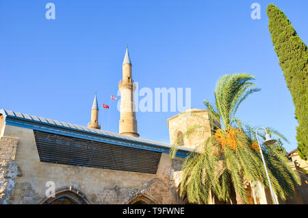 Muslim Selimiye Mosque in Nicosia, Northern Cyprus taken from below with blue sky and green trees around. Originally Roman Catholic Cathedral - Stock Photo