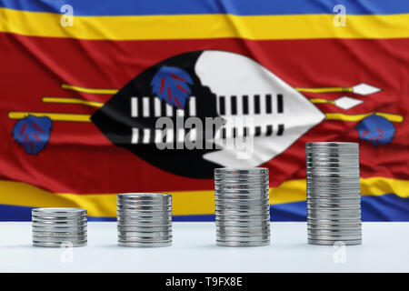 Wrinkled Swaziland flag in the background with rows of coins for finance and business concept. Saving money. - Stock Photo