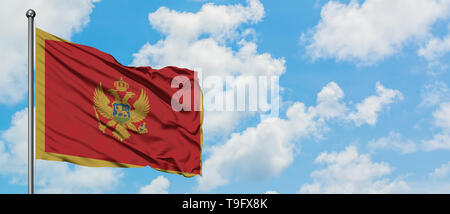 Montenegro flag waving in the wind against white cloudy blue sky. Diplomacy concept, international relations. - Stock Photo