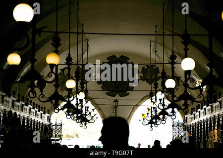 Krakow, Poland - September 23, 2018: Interior of gallery of Cloth Hall with visitors walking along the stalls. Focus on silhouettes and lamps. Cloth - Stock Photo