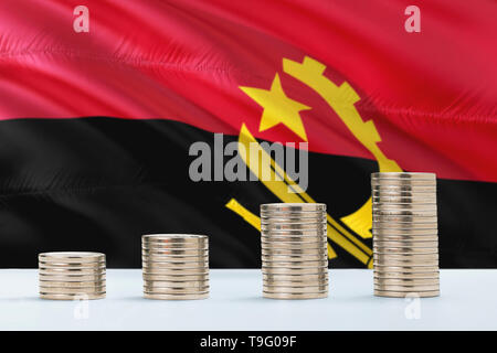 Angola flag waving in the background with rows of coins for finance and business concept. Saving money. - Stock Photo